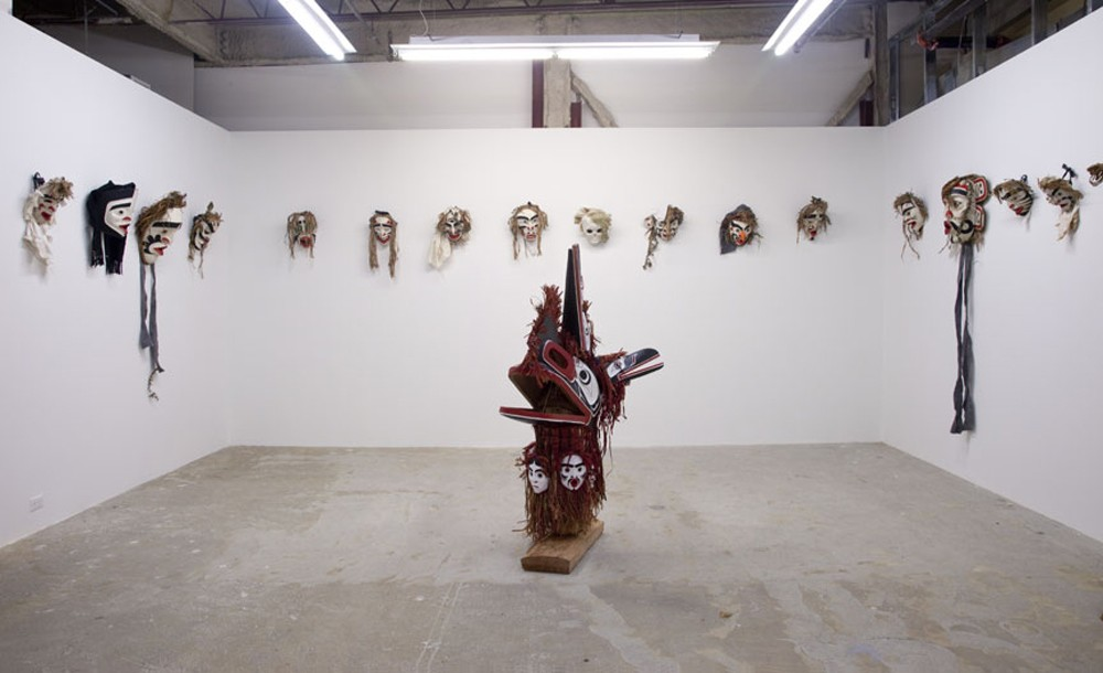 "Installation View of Atlakim Masks (dimensions variable) with Four and Face, 2012, 49""x66""x15"", cedar, paint"